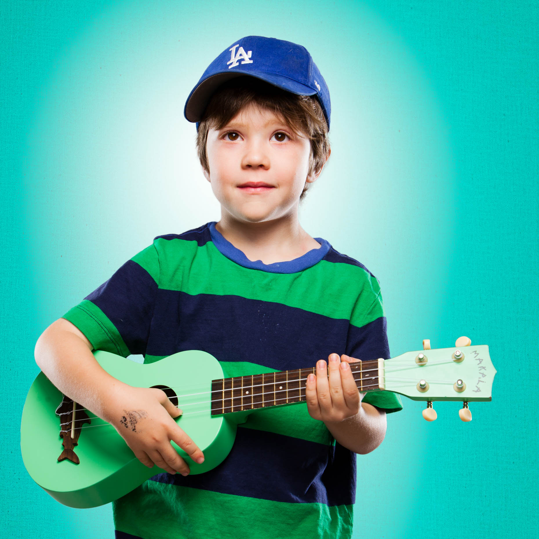 A studio portrait of a 6 year old boy, who has an interest in playing his Ukulele. This portrait was created by Steve Glass, owner of Glass Photography Portrait Studio. In all of their portraits they are looking to uncover the unique interests, creativity and beauty that each person creates. This deepest portion of a person that is created in the image of God, the Imago Dei. Steve Glass, a professional portrait photographer of Glass Photography services the men, women, children, kids, families, business and people of Fort Collins, Windsor, Loveland, Wellington and the surrounding areas of Northern Colorado and southern Wyoming (and sometime Denver), through professional photography by creating timeless portraits and heirloom prints, ranging from corporate portraits, corporate headshots, environmental portraits, editorial portraits, and beauty portraits.