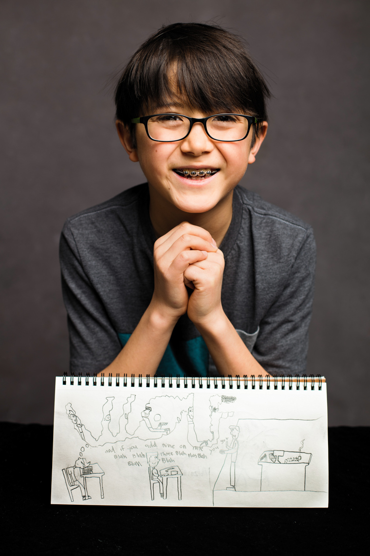 A studio portrait of a strong, handsome 9-year-old boy who loves tall tales, stories and a good conversation. He is surrounded by comics that he drew. He wants to be a comic or a writer someday – or both. This portrait was created by Steve Glass, owner of Glass Photography Portrait Studio. In all, of his portraits he is seeking the Imago Dei – the image of God – in each of his subjects. This means uncovering the unique interests, creativity, ingenuity and beauty that each person possesses. This deepest portion of a person that is created in the image of God, the Imago Dei. Steve Glass, a professional portrait photographer of Glass Photography services the men, women, children, kids, families, business and people of Fort Collins, Windsor, Loveland, Wellington and the surrounding areas of Northern Colorado and southern Wyoming (and sometime Denver), through professional photography by creating timeless portraits and heirloom prints, ranging from corporate portraits, corporate headshots, environmental portraits, editorial portraits, and beauty portraits.