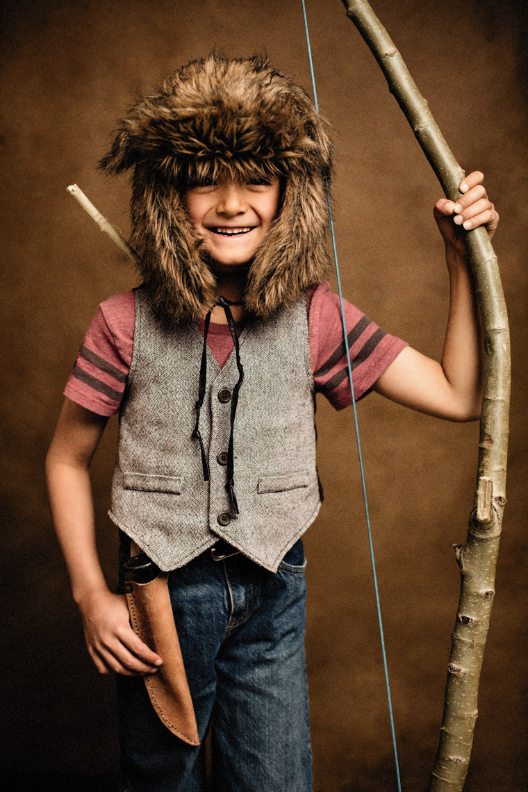 A studio portrait of a strong, handsome 7-year-old boy who is a mountain man at hat. Here he wears his mountain man vest, a pelt hat, and has a bow and arrow that he made. Someday he wants to build a cabin and live in the middle of the woods. This portrait was created by Steve Glass, owner of Glass Photography Portrait Studio. In all, of his portraits he is seeking the Imago Dei – the image of God – in each of his subjects. This means uncovering the unique interests, creativity, ingenuity and beauty that each person possesses. This deepest portion of a person that is created in the image of God, the Imago Dei. Steve Glass, a professional portrait photographer of Glass Photography services the men, women, children, kids, families, business and people of Fort Collins, Windsor, Loveland, Wellington and the surrounding areas of Northern Colorado and southern Wyoming (and sometime Denver), through professional photography by creating timeless portraits and heirloom prints, ranging from corporate portraits, corporate headshots, environmental portraits, editorial portraits, and beauty portraits.