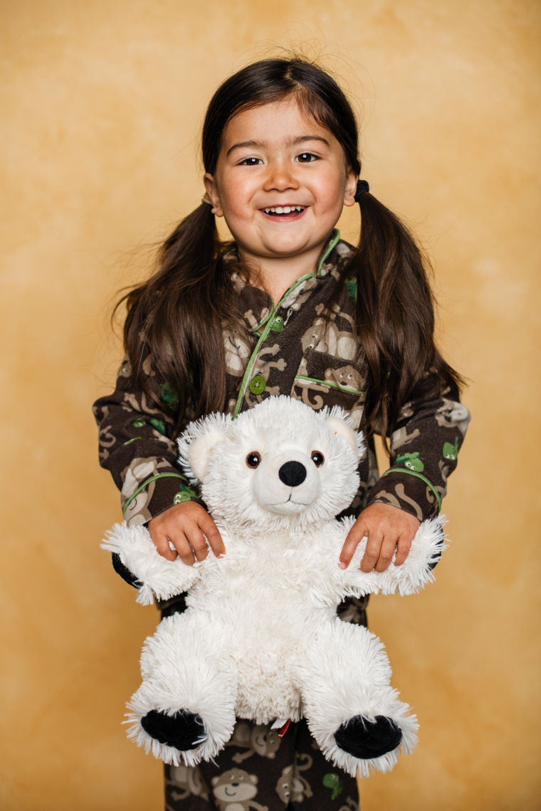 A studio portrait of an adorable cute 3-year-old girl who loves wearing her monkey pajamas and playing with her stuffed polar bear. This portrait was created by Steve Glass, owner of Glass Photography Portrait Studio. In all of his portraits he is seeking the Imago Dei – the image of God – in each of his subjects. This means uncovering the unique interests, creativity, ingenuity and beauty that each person possesses. This deepest portion of a person that is created in the image of God, the Imago Dei. Steve Glass, a professional portrait photographer of Glass Photography services the men, women, children, kids, families, business and people of Fort Collins, Windsor, Loveland, Wellington and the surrounding areas of Northern Colorado and southern Wyoming (and sometime Denver), through professional photography by creating timeless portraits and heirloom prints, ranging from corporate portraits, corporate headshots, environmental portraits, editorial portraits, and beauty portraits.