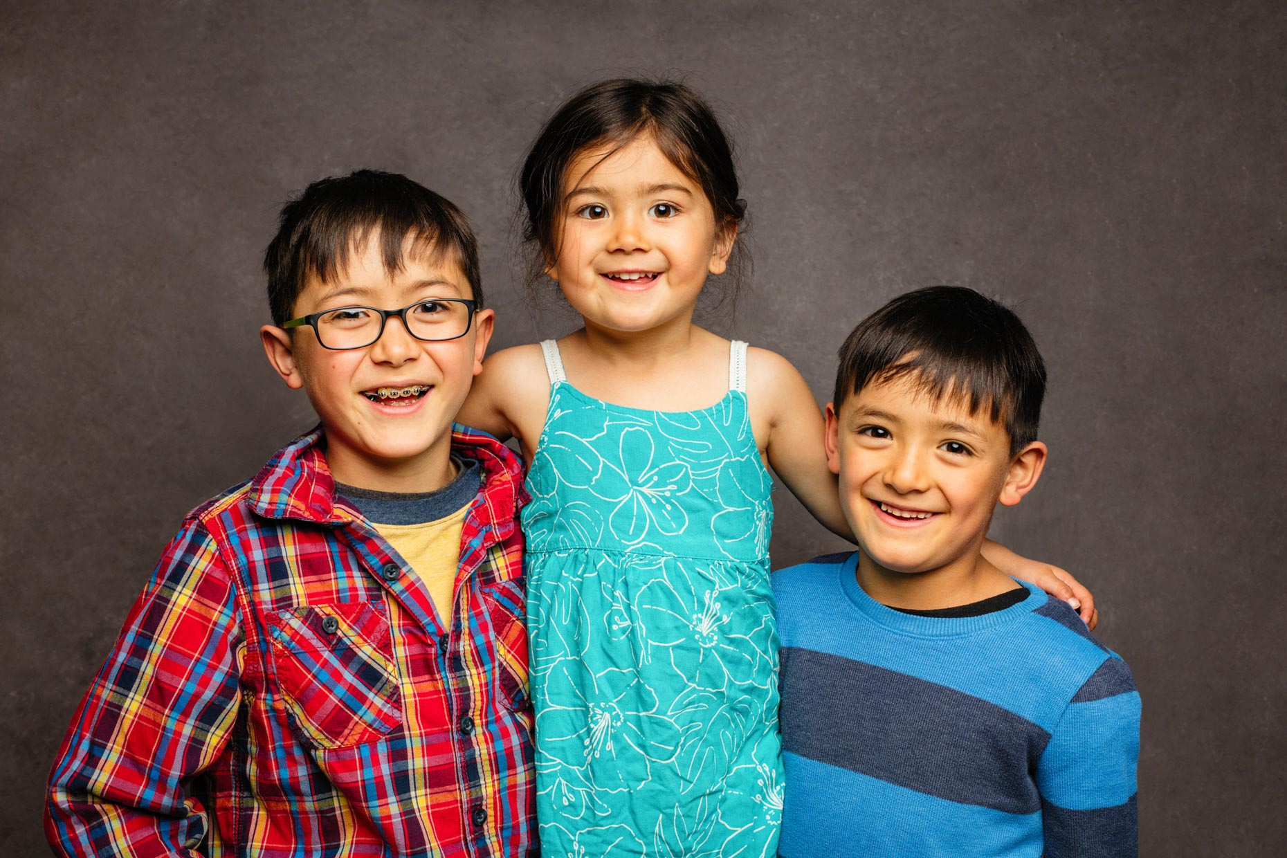 A studio portrait of three adorable (siblings) children. A  9 year old boy, a 3 year old girl and 7 year old boy. This portrait was created by Steve Glass, owner of Glass Photography Portrait Studio. In all of their portraits they are looking to uncover the unique interests, creativity and beauty that each person creates. This deepest portion of a person that is created in the image of God, the Imago Dei. Steve Glass, a professional portrait photographer of Glass Photography services the men, women, children, kids, families, business and people of Fort Collins, Windsor, Loveland, Wellington and the surrounding areas of Northern Colorado and southern Wyoming (and sometime Denver), through professional photography by creating timeless portraits and heirloom prints, ranging from corporate portraits, corporate headshots, environmental portraits, editorial portraits, and beauty portraits.