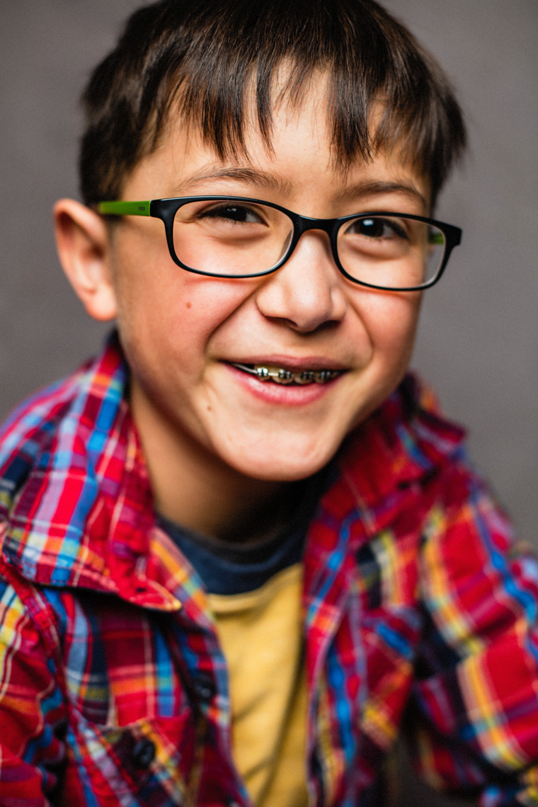 A studio portrait of a strong, handsome 9 year old boy. This portrait was created by Steve Glass, owner of Glass Photography Portrait Studio. In all of their portraits they are looking to uncover the unique interests, creativity and beauty that each person creates. This deepest portion of a person that is created in the image of God, the Imago Dei. Steve Glass, a professional portrait photographer of Glass Photography services the men, women, children, kids, families, business and people of Fort Collins, Windsor, Loveland, Wellington and the surrounding areas of Northern Colorado and southern Wyoming (and sometime Denver), through professional photography by creating timeless portraits and heirloom prints, ranging from corporate portraits, corporate headshots, environmental portraits, editorial portraits, and beauty portraits.