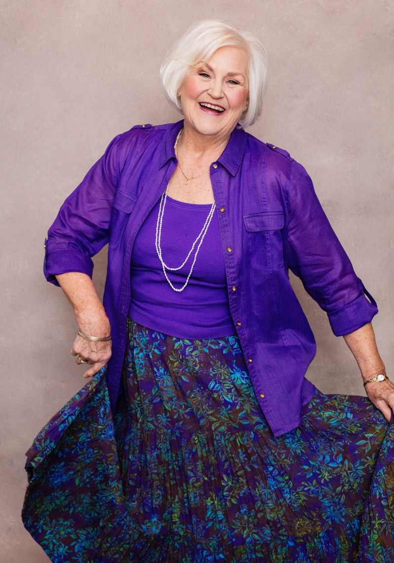 A beauty portrait of Kathryn Glass Addleman, a 75 year old, beautiful woman. This portrait was created by portrait photographer Steve Glass in his portrait studio Glass Photography through their beauty portrait service (a makeover portrait) session, where professional hair, professional makeup, professional styling are provided in the sitting fee. Kathy is wearing a purple skirt and purple blouse. The portrait reveals her beauty, her femininity, her soul, her fun spirit, her beauty, her fabulous personality. Steve Glass, is a professional portrait photographer of Glass Photography where he services the men, women, children, kids, families, business and people of Fort Collins, Windsor, Loveland, Wellington and the surrounding areas of Northern Colorado and southern Wyoming (and sometime Denver), through professional photography by creating timeless portraits and heirloom prints, ranging from corporate portraits, corporate headshots, environmental portraits, editorial portraits, and beauty portraits.